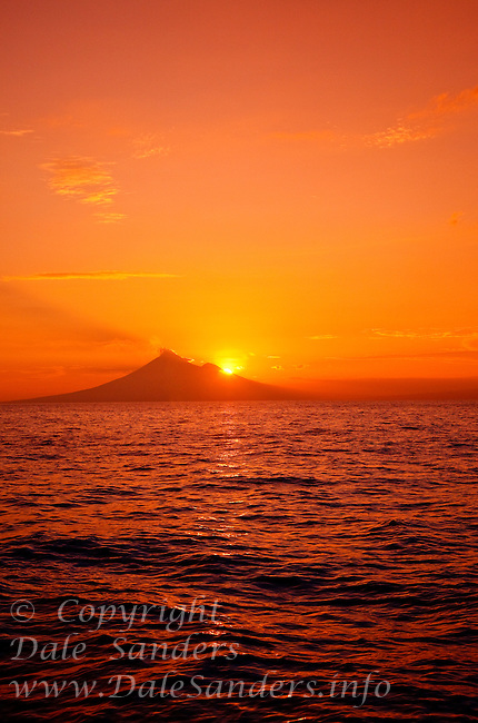 """The morning sun rising behind a distant volcano... as seen from a dive site in the Fathers Reefs off New Britain Island, Papua New Guinea. A small tendril of steam rising from the 2,334 meter high summit of Mount Ulawan is a gentle reminder that we are diving in Papua New Guinea's  """"Ring of Fire"""".  Papua New Guinea has over sixty volcanoes strewn across its vast archipelago… nineteen exist on New Britain Island alone… and five of those are currently active."""