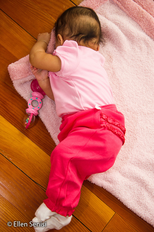MR / Schenectady, NY. Infant (girl, 4 months, African American & Caucasian) exhibits 4-month-old human development milestone behavior as she rolls over from lying on her back to her stomach. MR: Dal4. ID: AL-HD. © Ellen B. Senisi