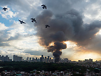 A huge plume of smoke of a fire that lasted some 8 hours in the Mandaluyong suburb of Manila with the Makati Business skyline behind. Some 2000 families lost their homes on that day, Nov.29th 2019. Philippines Birds flying past the smoke