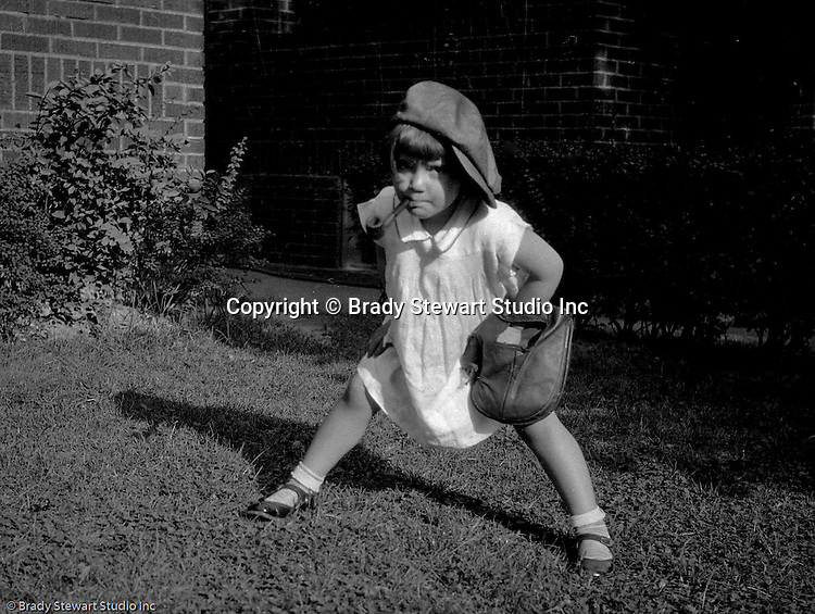 Wilkinsburg PA: Sally Stewart playing baseball in the backyard with her brother Brady. She is using one of her father's old baseball gloves from the 1900s.