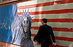 """A man walks past murals lining the walls surrounding the US Den of Espionage, the former US embassy in Tehran.  (This is where CIA lead their coup d'etat """"Operation Ajax"""" that brought down Mossadegh's democratically elected government and installed one more favorable to British and American interests.)"""