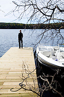 A modern speedboat is moored beside the jetty where owner and architect Renee Daoust is standing admiring the view of the lake
