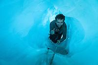 Happy tourist crawling through ice cave on Franz Josef Glacier, Westland NP, West Coast, New Zealand