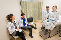 Alaska WWAMI Program students Kenton Stephens, Shannon Royal, and Hope Spargo examine a patient model in the UAA Health Sciences Building simulation lab.