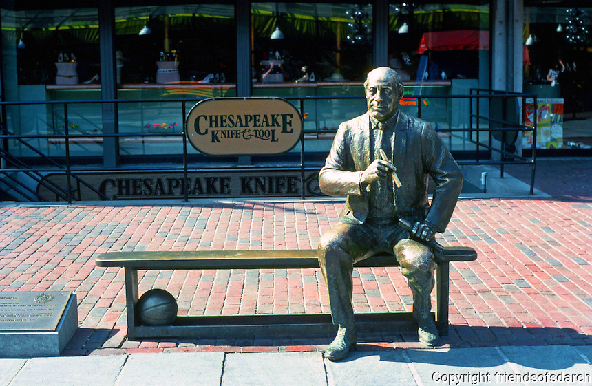 """Boston:  Faneuil Hall Markets--Red Auerback Sculpture.  Red was  personification of basketball's greatest dynasty, the Boston Celtics.  Sculptor Lloyd Lillie, 1985.  Bench encourages  """"sit-by-me"""".   Photo '88."""