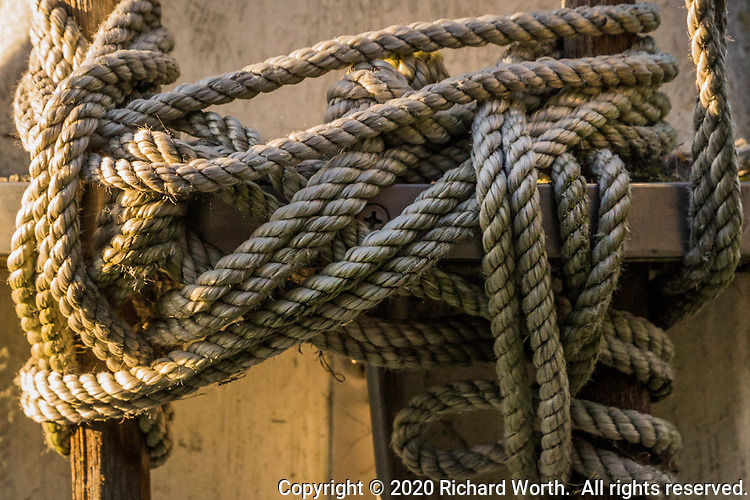 In a close-up detail, the rigging at the bottom of a yacht club flag pole.  The pole is in the form of a sailboat mast.