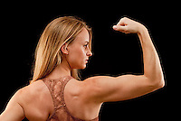 Woman with arm raised, flexing muscle, waist up, rear view