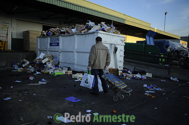 A people collects trash food away to celebrate New Year's Eve in Madrid's main food market, one of the biggest in the world, on December 31, 2011 the poor scavenge for discarded fruit for free food. Hunting Among the delivery trucks at the Mercamadrid, Their plight is bleak Evidence of Spain's stalled economy, and a queue of five million jobless people. (c) Pedro ARMESTRE