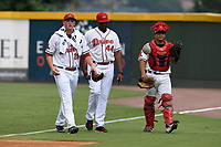 Starting pitcher Jay Groome (28) of the Greenville Drive, left, walks in from the bullpen with pitching coach Walter Miranda (44) and catcher Isaias Lucena (19) before a game against the Hickory Crawdads on Sunday, July 16, 2017, at Fluor Field at the West End in Greenville, South Carolina. Hickory won, 3-1. (Tom Priddy/Four Seam Images)