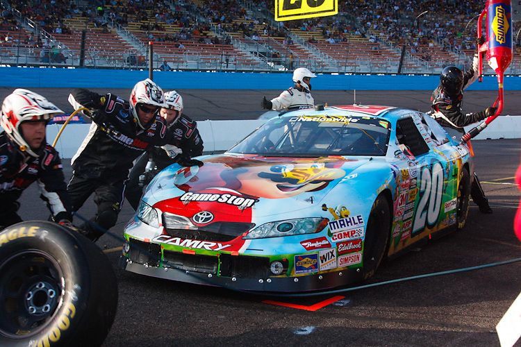 Nov. 14, 2009, Phoenix, AZ: Crew members scramble to change tires and add fuel to Denny Hamlin's number 20 in the pits before his wreck with Brad Keselowski.