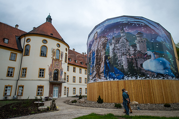"26 April 2018, Germany, Ettal: People pass a snow-globe-themed picture featuring King Ludwig II at the ""Holz erleben"" (lit. ""Experience wood"") pavillion in the grounds of Ettal Abbey. The Bayerische Landesausstellung 2018 (lit. Bavarian State Exhibition 2018) is set to open on 02 May. Photo: Lino Mirgeler/dpa"