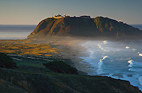 Dawn-Lit Waves at Point Sur Lighthouse, along the Big Sur coast, with lighthouse spotlight shining and gentle surf moving in towards a beach with the Pacific Ocean horizon in the distance.