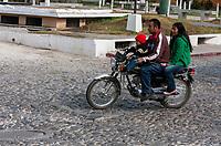 Antigua, Guatemala.  Parents and Son on Motorbike, no Helmet.