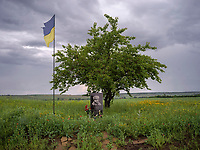 A flags flies over a memorial site at the place where a Ukrainian soldier was killed in fighting with Russian-backed separatists.