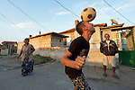 """THIS PHOTO IS AVAILABLE AS A PRINT OR FOR PERSONAL USE. CLICK ON """"ADD TO CART"""" TO SEE PRICING OPTIONS.   A man heads a soccer ball while playing football in the street in the largely Roma neighborhood of Gorno Ezerovo, part of the Bulgarian city of Burgas. Residents here don't self-identify much as Roma, because of the negative connotations associated with the word, so many refer to themselves as a Turkish-speaking minority."""