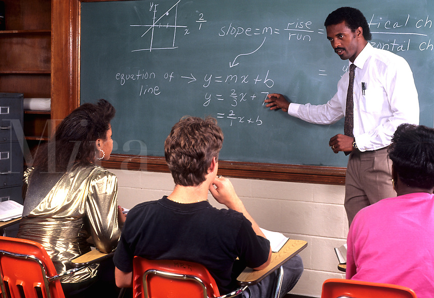 Black professional teacher in front of class teaching math to students in schoo