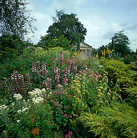 In the gardens of an English country house a neo-classical temple can just be seen behind large beds of flowering perennials