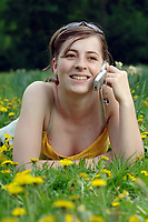Germany, Berlin. Woman on a meadow using her mobile phone. 08.05.2006    *** Local Caption *** 00829731