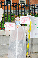 """A demonstrator wearing PPE including a facemask and face shield holds a sign reading """"Only when it's safe"""" and """"My first day of school outfit"""" as people gathered outside the Massachusetts State House for a protest organized by the Massachusetts Teachers Association against current school reopening plans during the ongoing Coronavirus (COVID-19) global pandemic in Boston, Massachusetts, on Wed., Aug. 19, 2020. The teachers' union, alongside two other Massachusetts teachers' unions, organized the event as part of a mass day of action demanding that the school year starts with remote learning and switch to in-person learning only when health and safety standards can be guaranteed."""