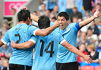 July 26, 2012..Uruguay's Ramon Arias (2), Uruguay's Nicolas Lodeiro (14), Uruguay's Luis Suarez (9) celebrate a goal. UAE vs Uruguay Football match during 2012 Olympic Games at Old Trafford in Manchester, England. Uruguay defeat United Arab Emirates 2-1...