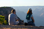 MAN AND WOMAN ON RIM OF GRAND CANYON WATCH THE SUN GO DOWN