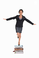 Businesswoman standing on one leg on files (Licence this image exclusively with Getty: http://www.gettyimages.com/detail/103732092 )