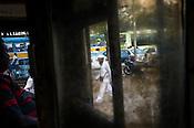 Pedestrians pass a parked Calcutta Tram at a depot in Kolkata, West Bengal, India.