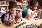 Education preschool 4 year olds girl and boy sorting colored plastic cubes into a pattern by color, boy creating color pattern with colored plastic bears