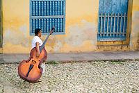 Man walking down Simon Bolivar and carrying a cello, Trinidad, Cuba.