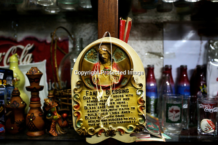 Antique Catholic items seen with Retro Coa-Cola memorabilia seen  available for sale at Angel Spirits Antique Store in Cubao Expo in Quezon city in Manila, Philippines. Photo: Sanjit Das