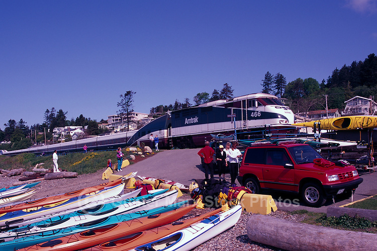 Kayaks on Beach at Semiahoo Bay, White Rock, BC, British Columbia, Canada - Amtrak Train passing by at Railway Crossing