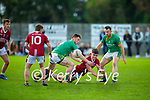 Cromane's Ethan Griffin passes the ball out of danger to team mate Shane Ahern under pressure from Timmy Moriarty and Maurice Slattery of Castlegregory in the Junior Football Championship Group 2 game