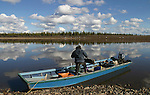 Vuntut Gwitchin First Nation hunter and trapper, Joel Peter, climbs into his boat to go caribou hunting on the Porcupine River near Old Crow, Yukon Territory, Canada.