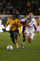 Los Angeles Galaxy defender Ugo Ihemelu dribbles away while  being pressured by New England Revolution midfielder Clint Dempsey. The New England Revolution beat the Los Angeles Galaxy at the Home Depot Center 1-0 in Carson, Calif. on April 1, 2006.