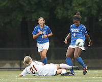 Boston College midfielder Kate McCarthy (21) slide tackle disrupts Duke University defender Natasha Anasi (4).Boston College (white) defeated Duke University (blue/white), 4-1, at Newton Campus Field, on October 6, 2013.