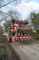 Tractor with sugar beet drill on narrow public road - Norfolk, March