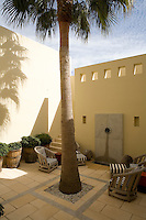 Seating is arranged on a secluded terrace garden with a simple fountain and under the shade of a solitary palm tree.