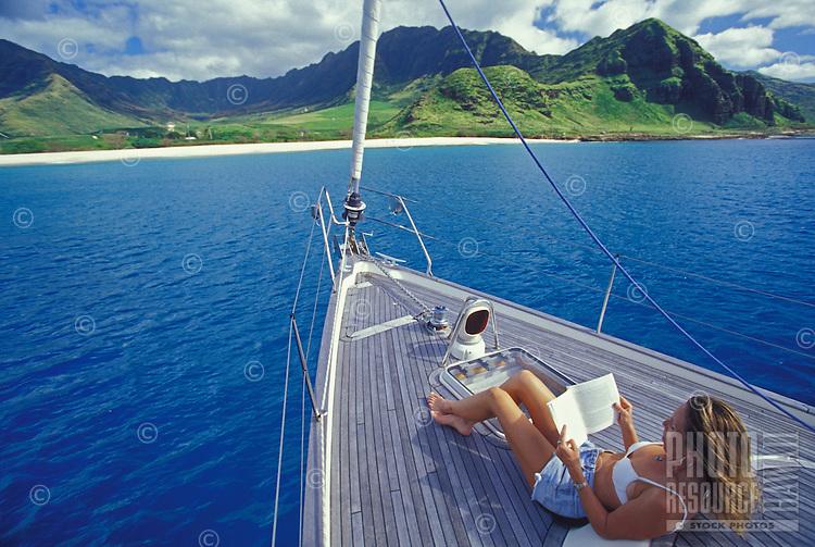 Woman reading on the bow of a sail boat off Oahu's leewaard coastline with Waianae mountain range in rear