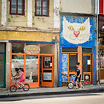 Children bicycle past a big cat face painted above an old shop, along the historic streets of Veliko Tarnovo, Bulgaria