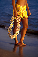 Hawaiian girl in sarong hold a yellow plumeria lei in Lahaina, Maui.