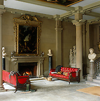 """Two red leather sofas flank the fireplace in the North Entrance Hall, which was the kitchen until the 1760s. """"Diana and her Nymphs surprised by Actaeon"""", 1650's, by Maratti and Dughet hangs above the fireplace"""