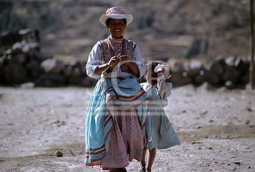 Achoma, Peru. Smiling woman in traditional dress with embroidered waistcoat with her daughter.