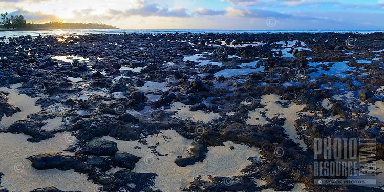 Sunrise over tide pools along a lava rock shoreline in Po'ipu, Kaua'i.