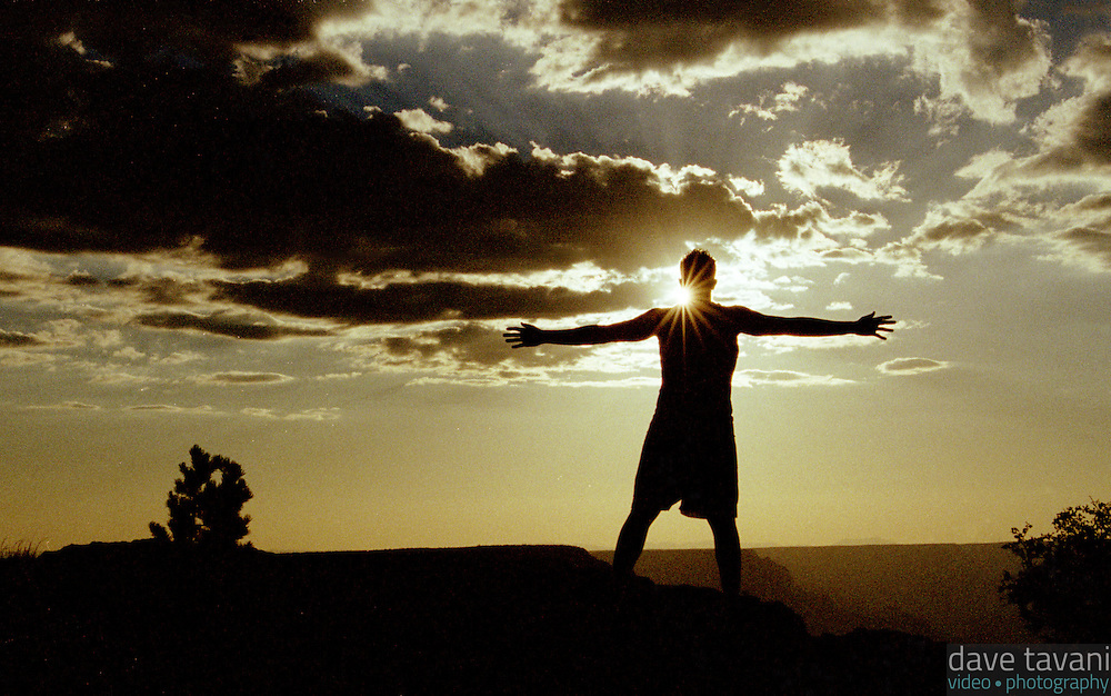 A young man stands silhouetted by the setting sun at the Southern Rim of the Grand Canyon, in Arizona.