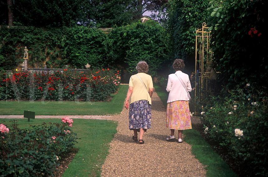 Two elderly ladies walking along garden pathway in Hever Castle Garden.  Hever Castle was home of Ann Boleyn, Henry VIII's 2nd wife.  Edenbridge, Kent, UK