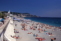 Nice, Cote d' Azur, France, Provence, Alpes-Maritimes, Europe, Sunbathing on the beach along the Promenade des Anglais on the Mediterranean Sea in the city of Nice.
