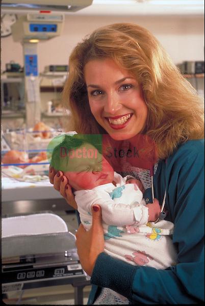 smiling nurse holding infant in hospital nursery