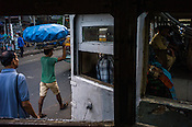A labourer carries load on his head next to a moving Calcutta Tram in Kolkata, West Bengal, India,