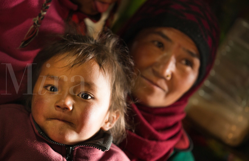 Nepal Himalayas  Sherpa mother holds child in home in Namche Bazarre remote Mt Everest 75