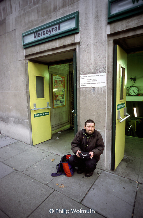 Unemployed homeless man begs outside a Merseyrail train station in Central Liverpool.